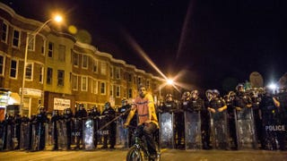 A protester sits in front of riot police minutes before a mandatory, citywide 10 p.m. curfew in Baltimore April 28, 2015, near the CVS pharmacy that was set on fire the day before during violent unrest after the funeral of Freddie Gray.Andrew Burton/Getty Images