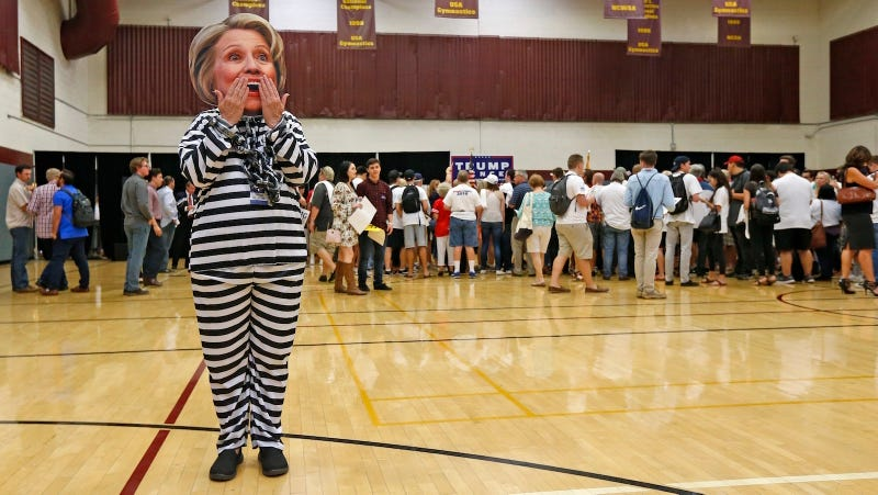 A Trump supporter wears a Hillary Clinton mask and prison jumpsuit at a campaign rally in Tempe, Arizona on Oct. 27, 2016. (Image via AP Photo/Ross D. Franklin).