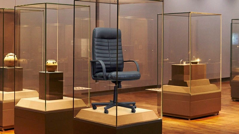 An office chair in a glass case.