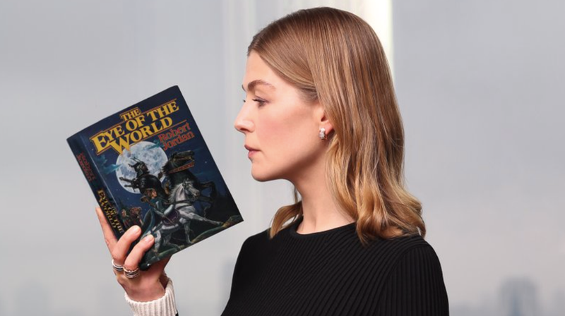 Rosamund Pike holding a copy of The Eye of the World.