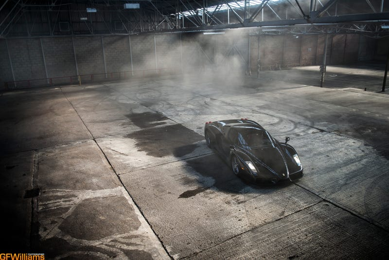 Illustration for article titled Watch This Black Ferrari Enzo Do Gratuitous Donuts In A Warehouse