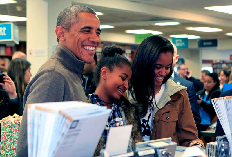 U.S. President Barack Obama and daughters Sasha (C) and Malia purchase books at Politics and Prose bookstore for 'Small Business Saturday' on November 29, 2014 in Washington, DC.