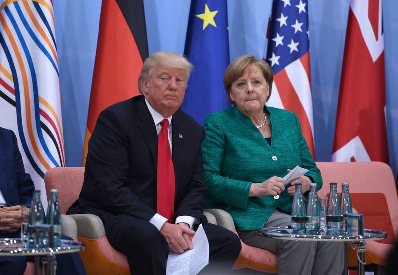 Trump, having no goddamned clue, with German Chancellor Angela Merkel (Photo: Patrik Stollarz/ Getty Images)