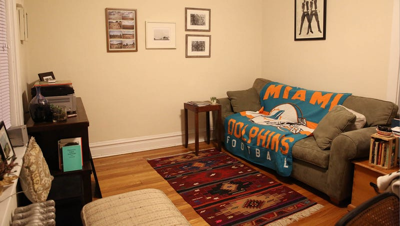 Illustration for article titled Carefully Thought-Out Living Room Decor Overshadowed By Enormous Blanket With Team Logo On It