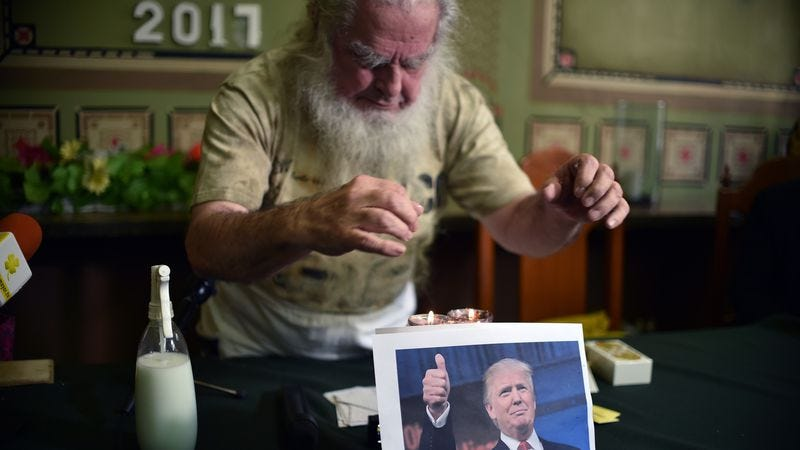 Antonio Vazquez, known as the 'Greatest Sorcerer' puts a spell on Donald Trump, represented by a picture during a ritual in Mexico City on January 5, 2017 (Photo: Yuri Cortez/AFP/Getty Images)