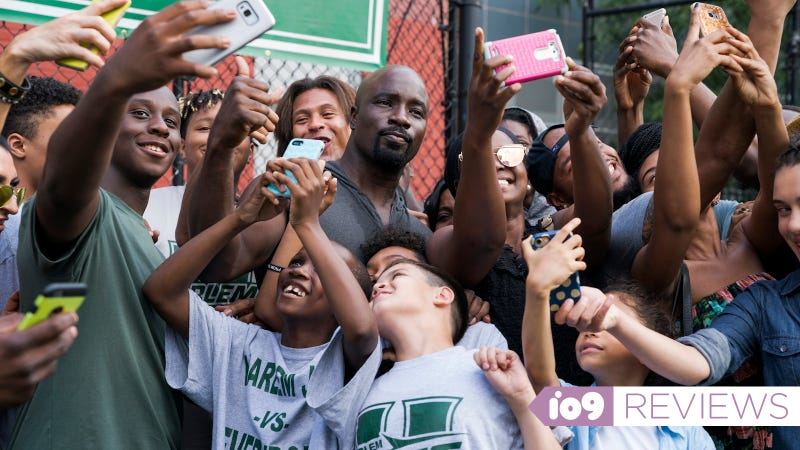 Mike Colter as Luke Cage posing for selfies with a group of neighborhood children.