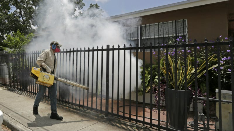 A Miami-Dade County mosquito control worker sprays around a home in the Wynwood area of Miami on Monday, Aug. 1, 2016. Photo via AP