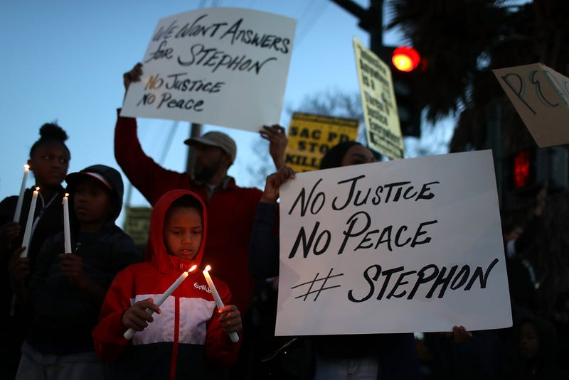 Black Lives Matter protesters hold candles during a vigil and demonstration on March 23, 2018, in Sacramento, Calif., in the wake of the fatal police shooting of Stephon Clark, an unarmed black man killed by Sacramento police in the backyard of his home.