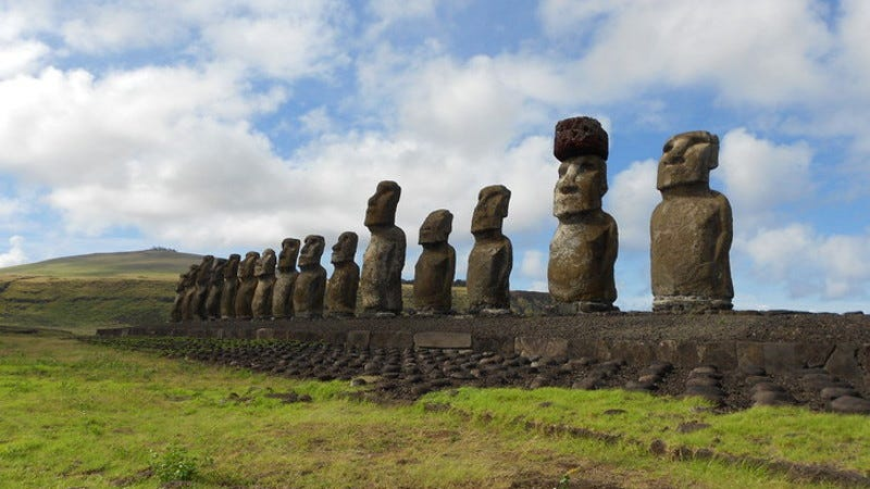 The statue platform with standing moai on the south coast of Rapa Nui. One of the moai is adorned with a red scoria pukao.