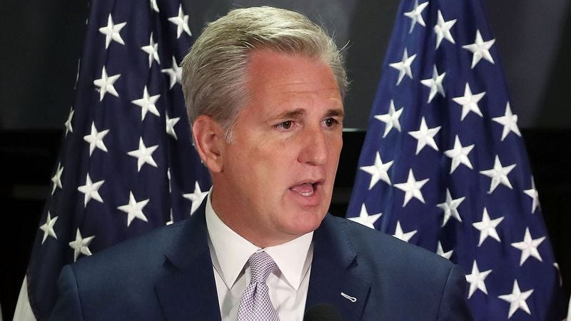 Senate Majority Leader Kevin McCarthy speaking with American flags as backdrop.