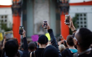 People aim cellphones at a speaker in front of the TCL Chinese Theatre on Hollywood Boulevard in Los Angeles on Dec. 6, 2014, as they march to protest the decision in New York not to indict a police officer involved in the choke hold death of Eric Garner in New York City.David McNew/Getty Images