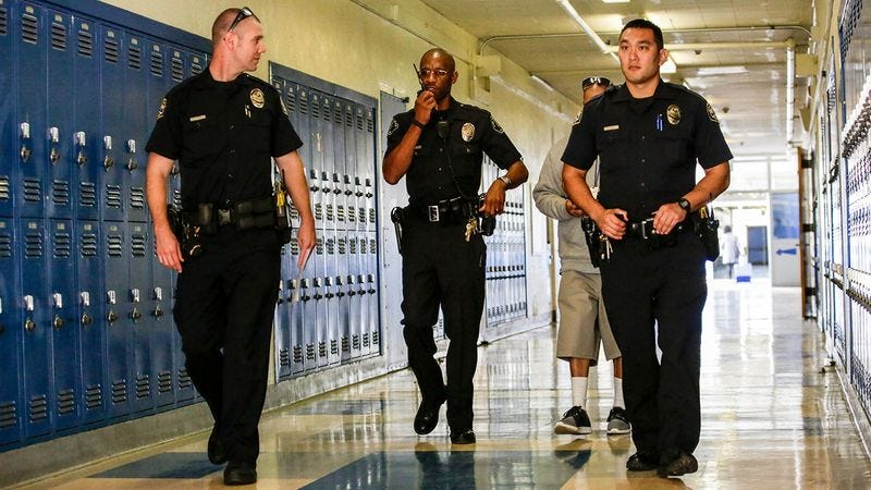 Police officers walking down a hallway of a school.