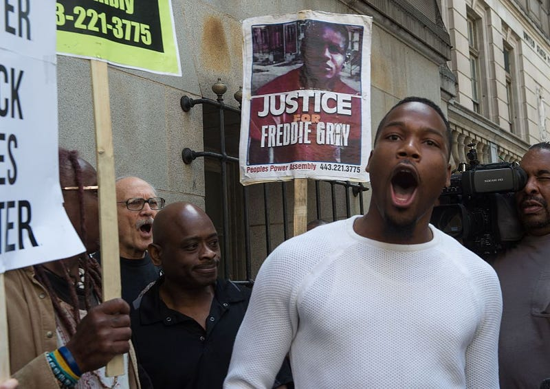 """Protestors chant after Baltimore police officer Edward Nero was cleared of all charges in the case of Freddie Gray, an African American who died in custody last year, sparking riots and fueling a nationwide debate about US police brutality, at the courthouse in Baltimore, Maryland, on May 23, 2016. The verdict handed down by a Baltimore judge found Officer Edward Nero not guilty of second-degree assault, of reckless endangerment or of misconduct in office. Outside the courthouse, a crowd of about a dozen protesters greeted the verdict with chants of """"No Justice, No Peace.""""       NICHOLAS KAMM/AFP/Getty Images"""