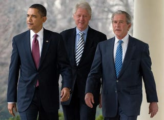 President Barack Obama walks down the West Wing Colonnade alongside former Presidents Bill Clinton and George W. Bush during a statement in the Rose Garden of the White House in Washington, D.C., on Jan. 16, 2010. SAUL LOEB/AFP/Getty Images