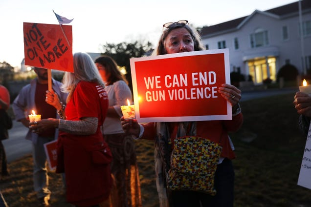 Dozens of people attend a vigil remembering the 59 people killed in shooting in Las Vegas and calling for action against guns on Oct. 4, 2017, in Newtown, Conn.