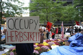 """Illustration for article titled """"Radiohead Wouldn't Play In The Big East Either"""": Occupy Wall Street Has An """"Occupy Herbstreit"""" Photobomber"""