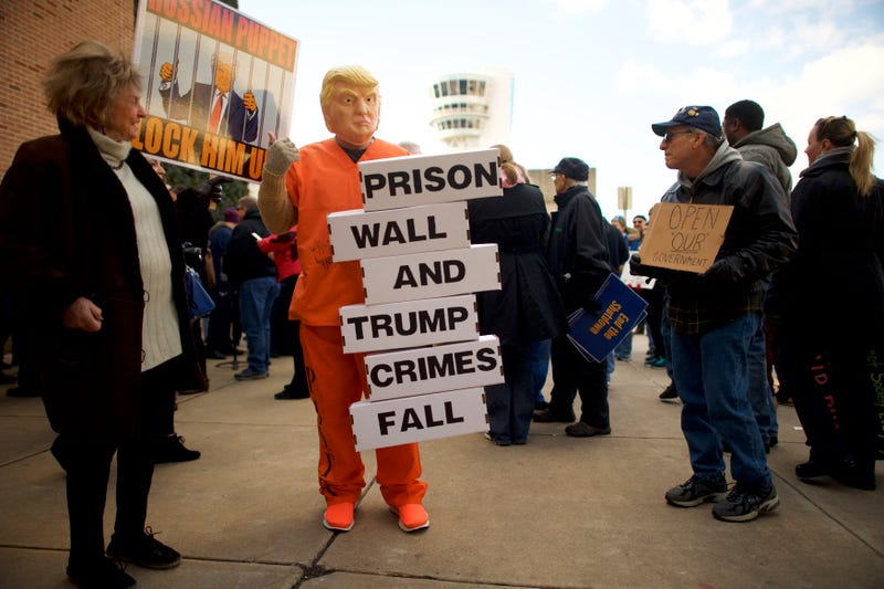 A protester dressed as President Donald Trump holds a placard stating 'PRISON WALL AND TRUMP CRIMES FALL' while demonstrating with Philadelphia Airport TSA and airport workers outside the Philadelphia International Airport on January 25, 2019 in Philadelphia, Pennsylvania. The government shutdown, now lasting 35 days, is the longest in United States history, affecting about 800,000 federal employees.