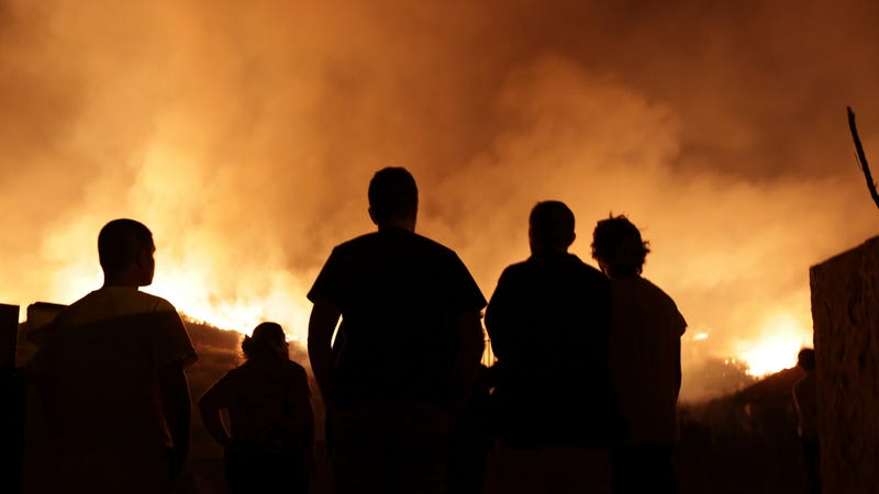 People watch a wildfire raging near houses in the outskirts of Obidos, Portugal, in the early hours of Monday, Oct. 16 2017. Photo: AP