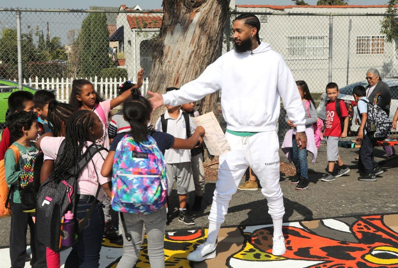 Nipsey Hussle greeting kids at an event to reveal a neighborhood basketball court he had worked to have refurbished, Oct. 22, 2018, in Los Angeles.