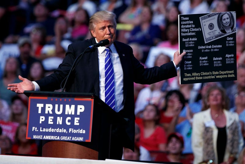 Donald Trump holds up a sign printed from the internet at a rally in Sunrise, Florida on August 10, 2016 (AP Photo/Evan Vucci)