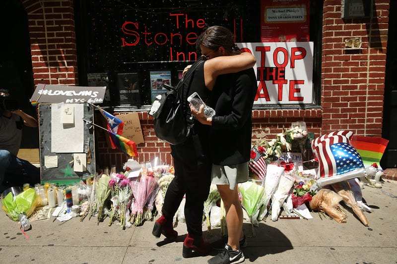 Matti Mejia and Shaina Roberts pause in front of the iconic gay and lesbian bar the Stonewall Inn in New York City on June 13, 2016, to lay flowers and grieve for those killed in Orlando, Fla. An American-born man who had recently pledged allegiance to the Islamic State group killed 49 people early June 12, 2016, at a gay nightclub in Orlando. The massacre is the deadliest mass shooting in U.S. history.Spencer Platt/Getty Images