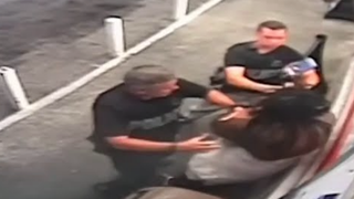 Video footage taken from a surveillance camera appears to show two Jacksonville, Fla., police officers grabbing Kelli Wilson and attempting to take her cellphone. Wilson says she was recording the officers as they were arresting her husband.  YouTube screenshot