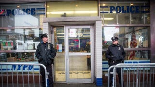 Police officers stand guard outside a New York City Police Department substation in Times Square Dec. 22, 2014, in New York City.Andrew Burton/Getty Images