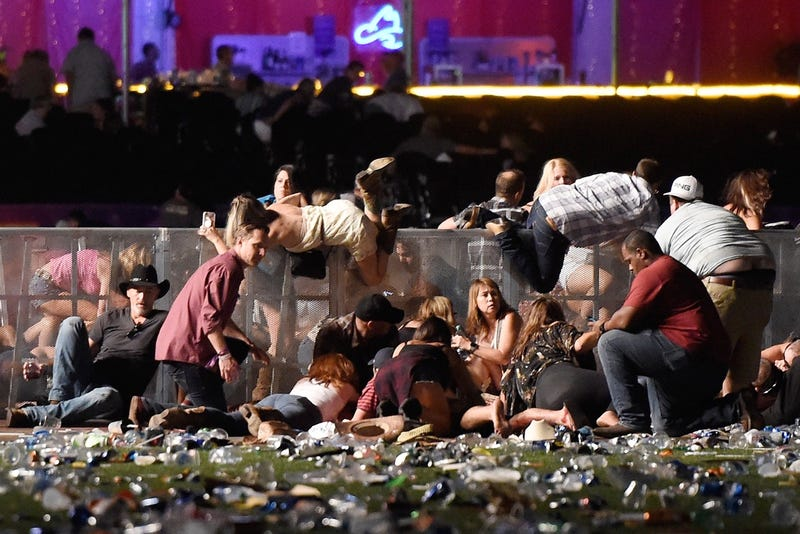 People scramble for shelter at the Route 91 Harvest country music festival after apparent gun fire was heard on October 1, 2017 in Las Vegas, Nevada. (Photo by David Becker/Getty Images)