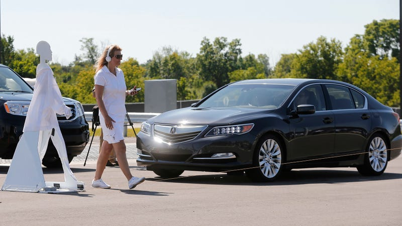 In this July 20, 2015 file photo, a pedestrian crosses in front of a vehicle as part of a demonstration at Mcity, used to test driverless and connected vehicles, on the University of Michigan campus in Ann Arbor, Mich.
