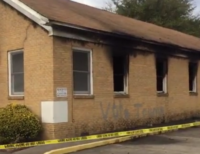 """The side of the Hopewell Missionary Baptist Church shows a badly burned part of the building, as well as the words """"Vote Trump"""" spray-painted on the building's side. Angie Quezada via Facebook"""