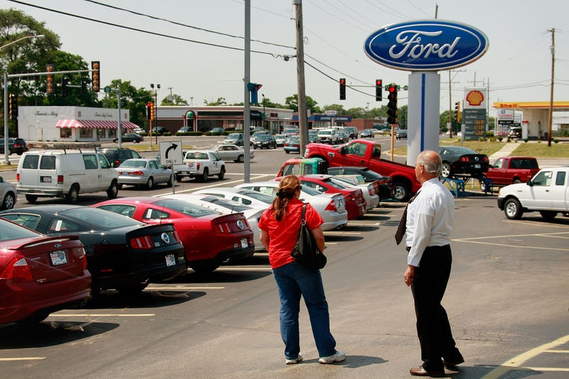 A car salesman with a customer at a Ford dealership in Downers Grove, Illinois. Image: Getty
