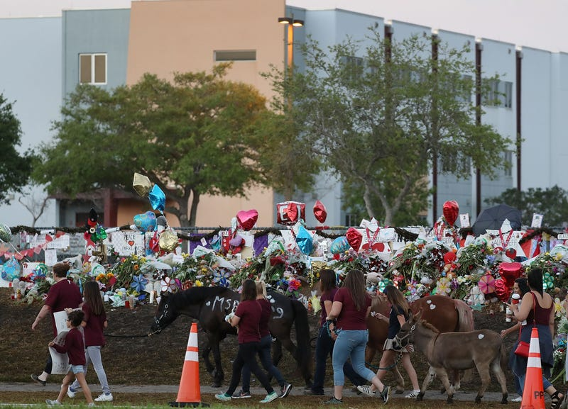 People arrive to offer support at Marjory Stoneman Douglas High School in Parkland, Fla., on Feb, 28, 2018, as students arrive to attend classes for the first time since the shooting that killed 17 people on Feb. 14 at the school.