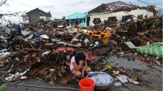 A girl washes clothes amid debris caused by Typhoon Haiyan in Leyte, Philippines. Dondi Tawatao/Getty Images