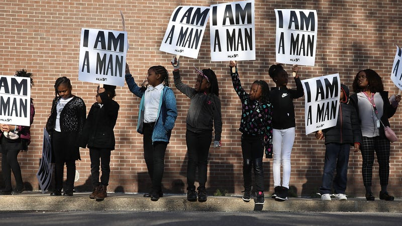 """Children from Promise Academy Spring Hill hold """"I Am a Man"""" signs, in reference to the Memphis, Tenn., sanitation workers' strike of 1968, as they participate in an event to mark the 50th anniversary of Martin Luther King Jr.'s assassination April 4, 2018, in Memphis. King was killed on April 4, 1968, while supporting the strike."""
