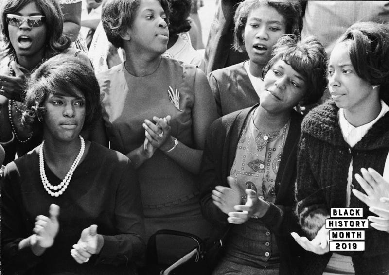 To pass the long morning, young women clap and sing along to a freedom song between speeches at the March on Washington for Jobs and Freedom, Washington DC, August 28, 1963.