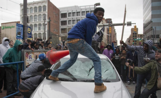 Allen Bullock, 18, turned himself in after he was photographed destroying a police car during the Freddie Gray unrest in Baltimore. His bail is currently set at $500,000—more than that of any of the six officers charged in Gray's death.NBC News screenshot