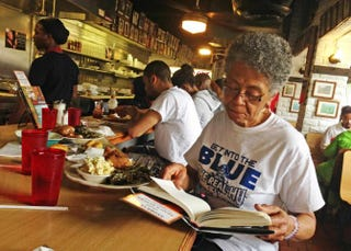 Martha Williams of Norfolk, Va., leafs through Soul Food: The Surprising Story of an American Cuisine, One Plate at a Time,by Adrian Miller, while having lunch at Florida Avenue Grill May 4, 2014, in Washington, D.C. Williams was in town visiting grandson Andrew Boyd Jr., who attends Howard University, and asked him where to go for some good soul food.Nicole L. Cvetnic/The Root