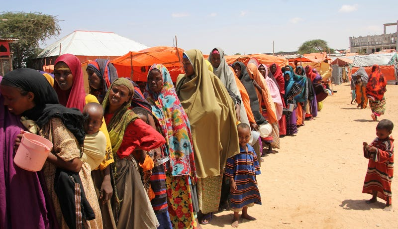 Displaced Somali women stand in line to receive food handouts on March 27, 2017. Image via AP Photo.