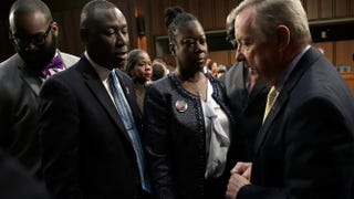Lawyer Benjamin Crump and Sybrina Fulton, mother of Trayvon Martin, greet Sen. Richard Durbin during a Senate Judiciary Committee hearing on 'Stand your ground' laws Oct. 29, 2013, in Washington, D.C.Win McNamee/Getty Images