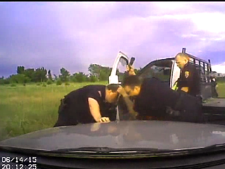 Scene from footage showing Owasso, Okla., Police Lt. Michael Dwain Denton slamming the butt of a shotgun toward the ground in June 14, 2015, incident.Tulsa World screenshot