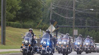 A police motorcade arrives at the funeral of Bobbi Kristina Brown at the St. James United Methodist Church Aug. 1, 2015, in Alpharetta, Ga.   David A. Smith/Getty Images