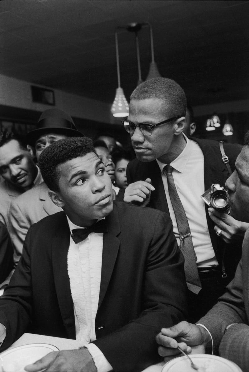 Malcolm X (right) teasingly leans on the shoulder of then-Cassius Clay, now Muhammad Ali, who is surrounded by jubilant fans after he beat Sonny Liston for the heavyweight championship of the world in 1964.Bob Gomel/the Life Images Collection/Getty Images