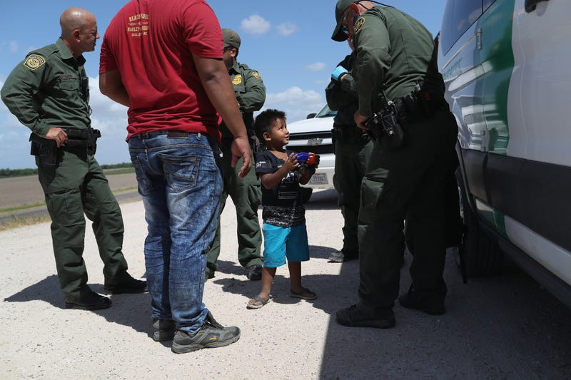 A boy and father from Honduras are taken into custody by U.S. Border Patrol agents near the U.S.-Mexico Border on June 12, 2018, near Mission, Texas.