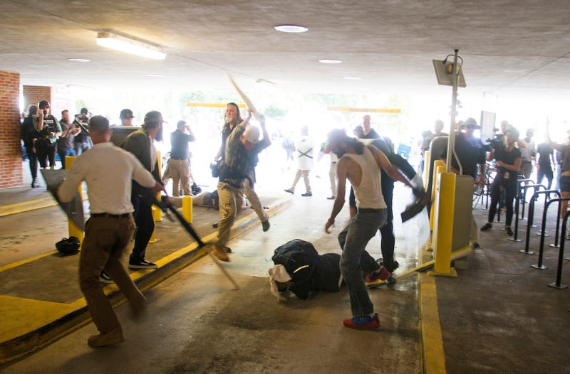 In this Aug. 12, 2017, photo, DeAndre Harris is assaulted in a parking garage beside a police station after a white nationalist rally was disbursed by police in Charlottesville, Va.