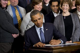 President Barack Obama signs a presidential memorandum increasing workers' overtime protections during an event in the East Room of the White House, March 13, 2014.SAUL LOEB/AFP/Getty Images