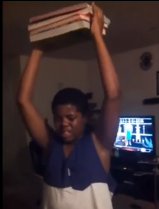 Boy holding books as punishment in YouTube videoWorldstarhiphop.com screenshot