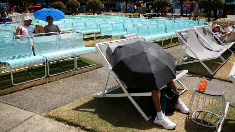 Spectators shielding themselves from the heat at Garden Square in Melbourne during the Australian Open tennis championships on Jan. 25, 2018.