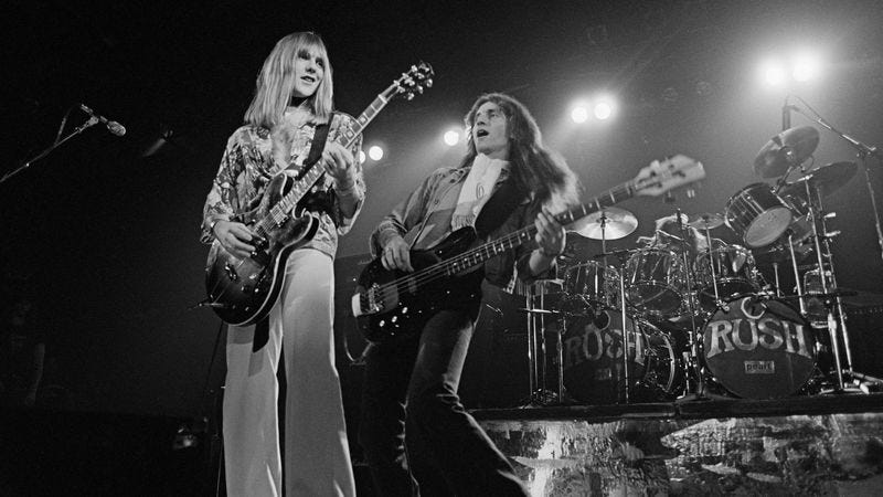 Alex Lifeson and Geddy Lee of Rush in 1976 during the All The World's A Stage Tour (Photo: Fin Costello/Redferns)