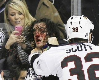 Illustration for article titled Hockey Player's Face Gets Bloodied While Lady With A Pink BlackBerry Cover Sort Of Watches
