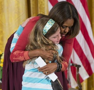 Michelle Obama hugs Charlotte Bell, 10, after she gave thefirst ladya copy of her father's resume. Charlotte's father has been out of work for three years.SAUL LOEB/AFP/Getty Images